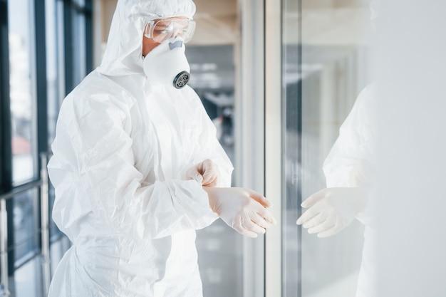 Lekarka naukowiec w fartuchu, okulary ochronne i maska stoi w pomieszczeniu i nosi rękawiczki