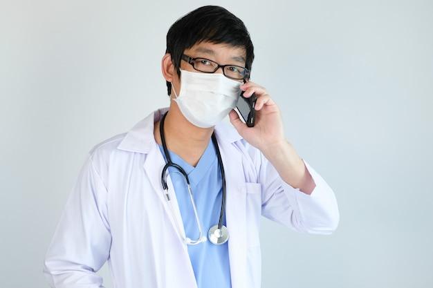Lekarka opowiada z smartphone z maską ochronną