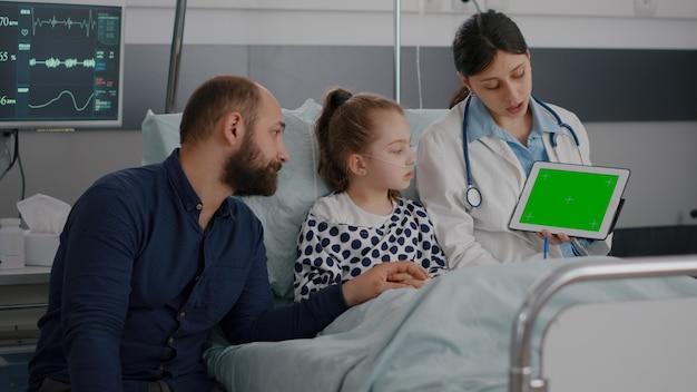 Lekarka pediatryczna trzymająca makietę tabletu chroma z zielonym ekranem z izolowanym wyświetlaczem