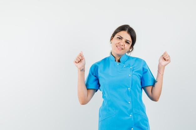 Lekarka pokazująca gest sukcesu w niebieskim mundurze i wyglądająca na szczęśliwą