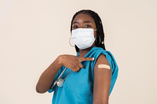 Lekarka pokazująca ramię z naklejką po otrzymaniu szczepionki