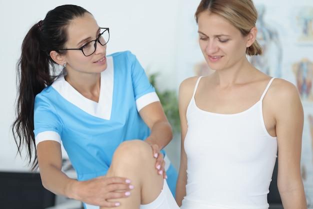 Lekarka przeprowadza badanie fizykalne stawu kolanowego pacjentki