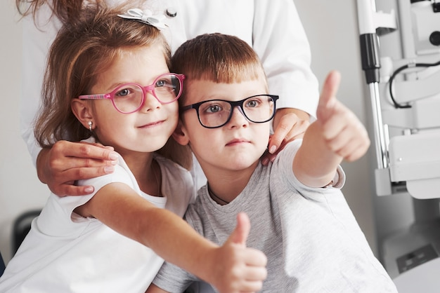 Lekarka przytula swoich małych pacjentów. okulary są idealnie dobrane.