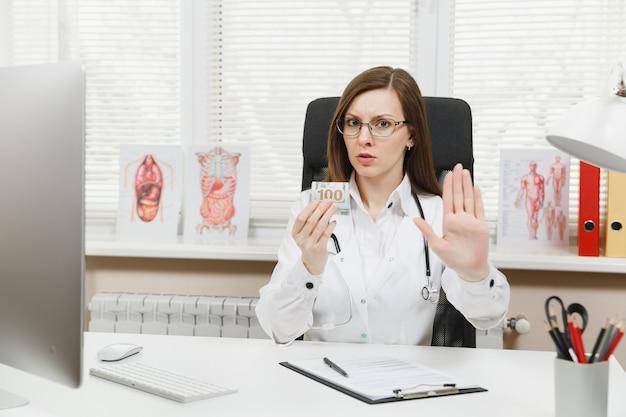"""Lekarka siedząca przy biurku trzymająca pakiet dolarów w gotówce, mówiąca """"nie"""" łapówce, pokazująca gest zatrzymania dłonią w gabinecie w szpitalu"""