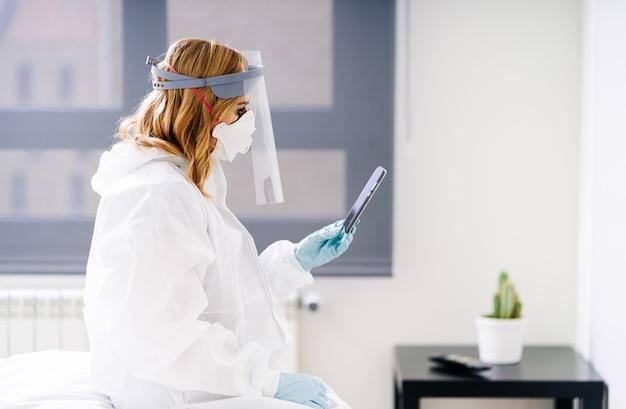 Lekarka siedzi w sali szpitalnej przy użyciu telefonu komórkowego