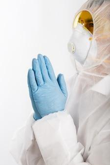 Lekarka w anty-epidemicznym kostiumu modleniu na białym tle