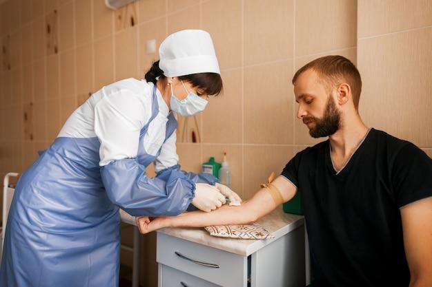 Lekarka w białej szacie robi zastrzyk młodemu mężczyźnie w sali zabiegowej szpitala.