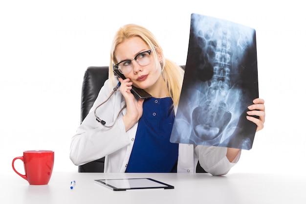 Lekarka w białym fartuchu dokładnie bada promieniowanie rentgenowskie