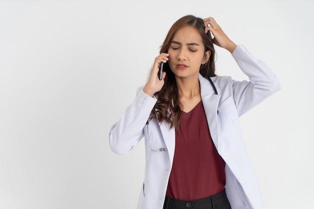 Lekarka w białym mundurze mylona z gestem zdenerwowania podczas rozmowy telefonicznej
