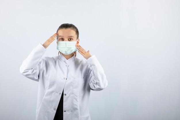 Lekarka w białym mundurze w masce medycznej