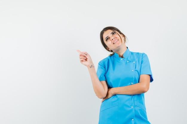 Lekarka w niebieskim mundurze, wskazująca na lewy górny róg i patrząca z nadzieją
