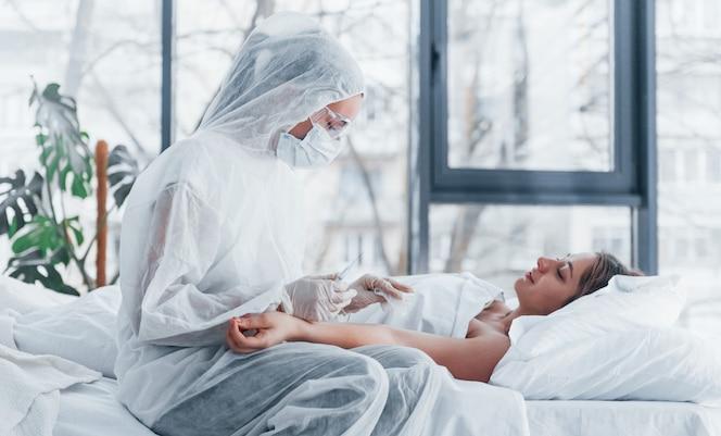 Lekarka w obronnym fartuchu i okulary ochronne ze strzykawką w ręku wstrzykiwanie leku do młodej dziewczyny chorej na wirusa