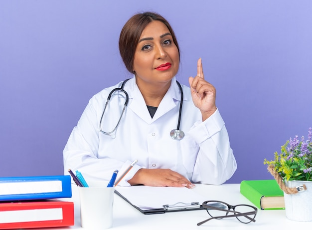 Lekarka w średnim wieku w białym fartuchu ze stetoskopem, patrząca pewnie, pokazując palec wskazujący jak ostrzeżenie, siedząca przy stole na niebieskim tle