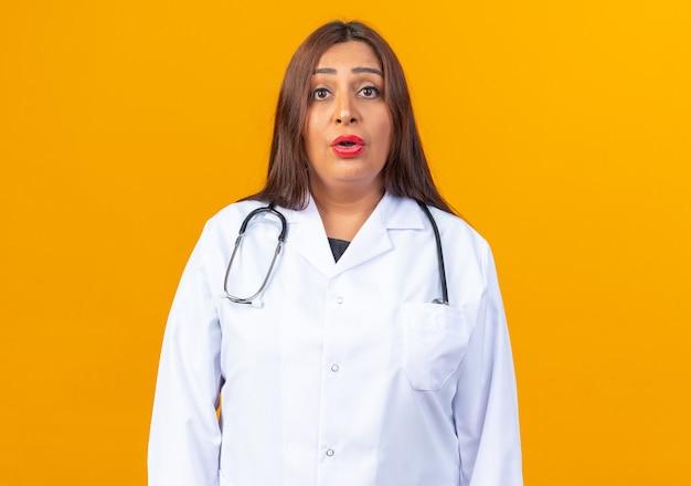 Lekarka w średnim wieku w białym fartuchu ze stetoskopem patrząca z zakłopotanym wyrazem twarzy