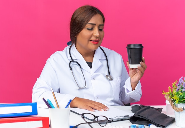 Lekarka w średnim wieku w białym fartuchu ze stetoskopem trzymająca filiżankę kawy patrzącą na schowek uśmiechnięta pewnie siedząca przy stole z folderami biurowymi na różowo