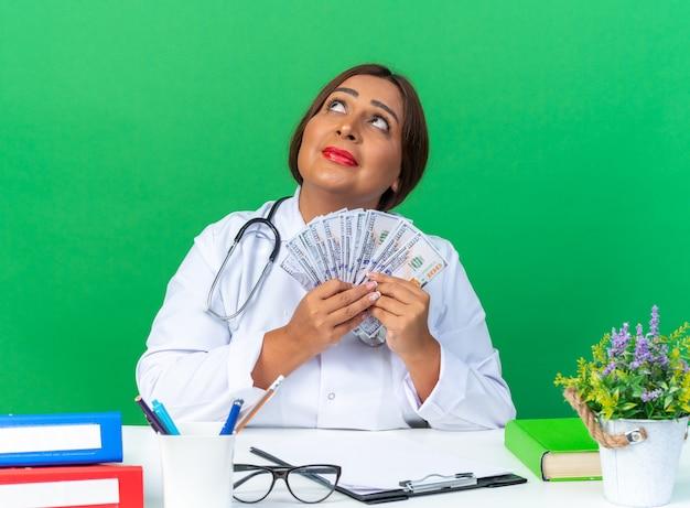 Lekarka w średnim wieku w białym fartuchu ze stetoskopem trzymająca gotówkę patrząca w górę szczęśliwa i pozytywna siedząca przy stole nad zieloną ścianą