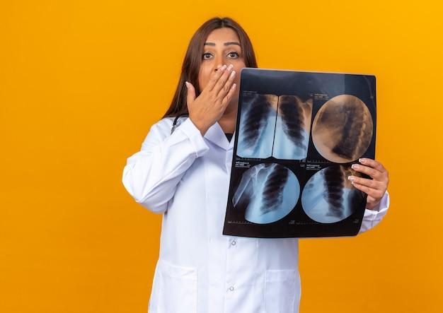 Lekarka w średnim wieku w białym fartuchu ze stetoskopem trzymająca prześwietlenie, patrząca z przodu, zszokowana, zakrywająca usta ręką stojącą nad pomarańczową ścianą