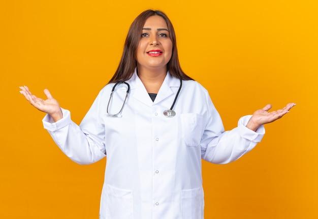 Lekarka w średnim wieku w białym fartuchu ze stetoskopem uśmiechnięta pewnie rozkładająca ręce na boki stojąca nad pomarańczową ścianą