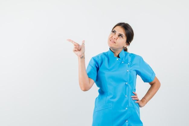 Lekarka wskazująca na bok, patrząc w górę w niebieskim mundurze