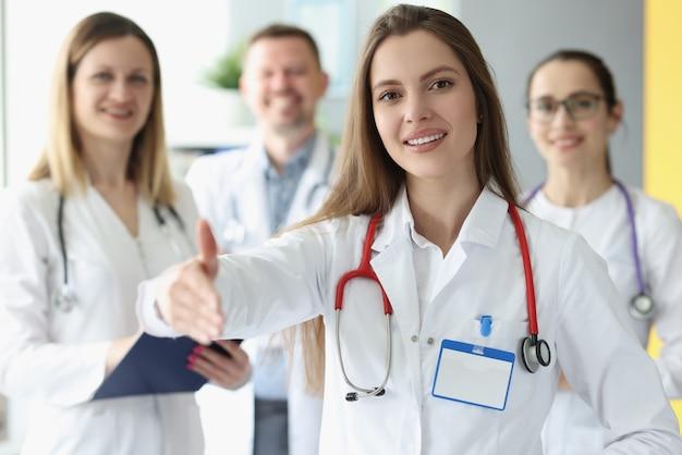Lekarka wyciąga rękę do uścisku dłoni z kolegami