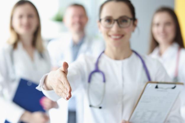 Lekarka wyciąga rękę po pozdrowienia na tle kolegów medycznych