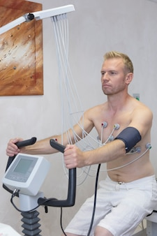 Lekarka z elektrokardiograma wyposażeniem robi kardiogramowi pod obciążenia testem męski pacjent w szpitalnej klinice