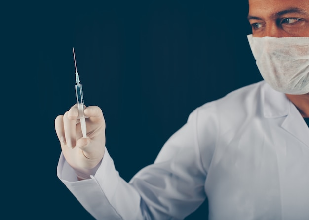 Lekarka z rękawiczkami i maskową mienie strzykawką w jego ręce. widok z boku.