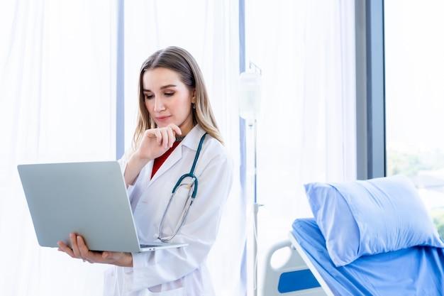 Lekarka ze stetoskopem pracuje z laptopem i pisze na papierkowej robocie na drewnianym stole w tle szpitala