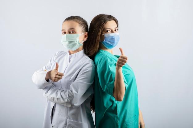 Lekarki w medycznych maskach pokazujące kciuk w górę