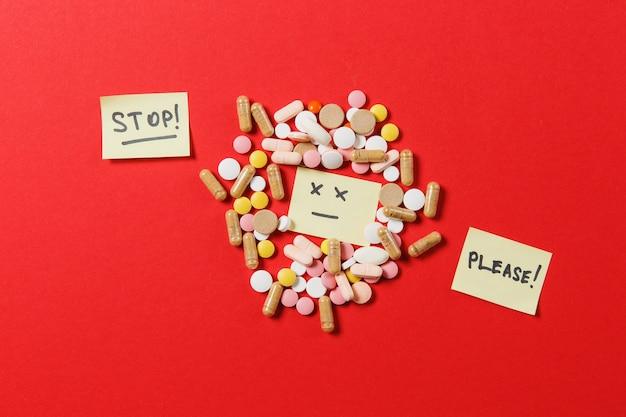 Lekarstwa białe kolorowe okrągłe tabletki ułożone abstrakcyjne na czerwonym tle koloru