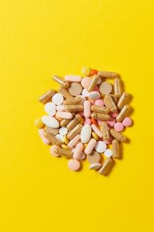 Lekarstwa białe kolorowe okrągłe tabletki ułożone abstrakcyjnie na żółtym tle koloru