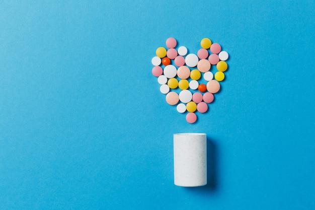 Lekarstwa białe, kolorowe okrągłe tabletki w formie serca na białym tle na niebieskim tle. pigułki o geometrycznym kształcie, butelka. pojęcie zdrowia, leczenia, wyboru, zdrowego stylu życia. skopiuj reklamę miejsca.