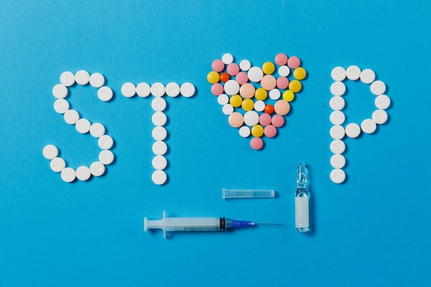 Lekarstwa białe, kolorowe okrągłe tabletki w słowie stop na białym tle na niebieskim tle