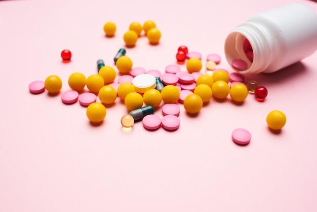 Lekarstwa posypane ze słoika na różowym tle zbliżenie farmaceutyki