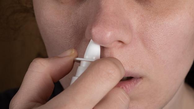 Lekarstwo na przeziębienie dziewczyna wciąga spray do nosa w nos