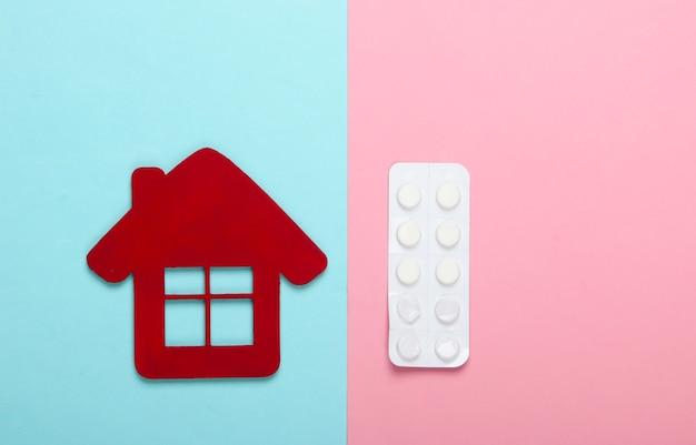 Lekarstwo w domu. leczenie w domu. figurka domu, blister tabletek na pastelowym niebiesko-różowym tle. widok z góry