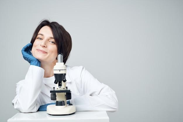 Lekarz asystent mikroskopu laboratoryjnego na uśmiechu stołu badawczego