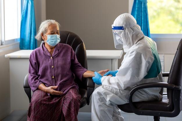 Lekarz azji sprawdza puls cierpliwości palcami, sprawdzanie medyczne na stole. starzejąca się pacjentka narażona na ryzyko zakażenia wirusem koronowym [covid-19].