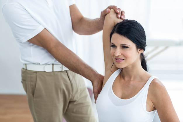 Lekarz bada fizjoterapię i daje kobiety w ciąży