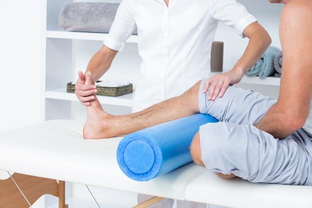 Lekarz bada jej nogę pacjenta