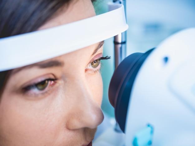 Lekarz bada oczy kobiety za pomocą maszyny pomiarowej.