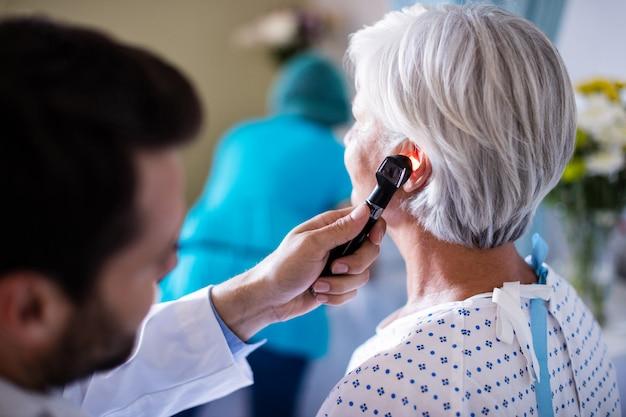 Lekarz bada pacjenta ucha z otoskopem