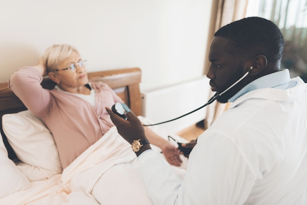 Lekarz bada starszego pacjenta w domu opieki
