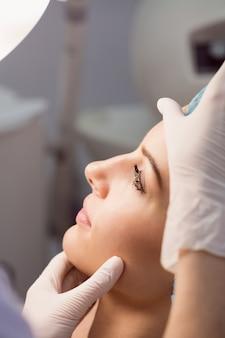 Lekarz bada twarz kobiety do zabiegu kosmetycznego