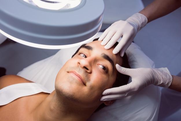 Lekarz bada twarz mężczyzny do zabiegu kosmetycznego