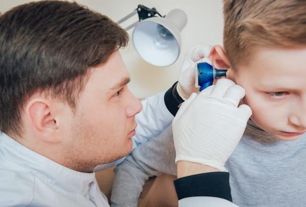 Lekarz bada ucho chłopca z otoskopem. wyposażenie medyczne.