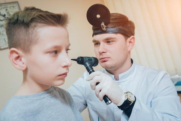 Lekarz bada ucho chłopca z otoskopem.