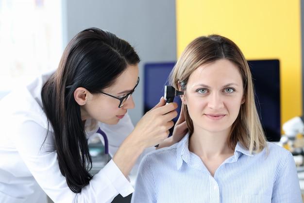 Lekarz bada ucho pacjenta otoskopem. koncepcja usług otolaryngologa