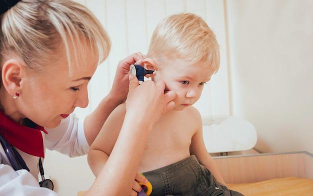 Lekarz bada ucho za pomocą otoskopu w pokoju pediatry.