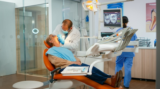 Lekarz bada zęby za pomocą instrumentów medycznych do pracy w rękawiczkach w nowoczesnej klinice dentystycznej. ortodonta rozmawia z kobietą siedzącą na fotelu stomatologicznym, podczas gdy pielęgniarka przygotowuje narzędzia do badania